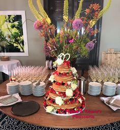 Naked cake met veel rood fruit en verse bloemen.