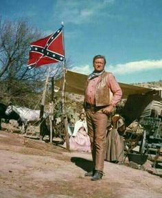 John Wayne poses with Confederate Flag in the background. John Wayne Quotes, John Wayne Movies, Southern Heritage, Southern Pride, Southern Living, Westerns, Confederate Flag, Confederate Monuments, John Ford