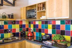 Cocina de un dúplex con azulejos de diferentes colores y mesada de cuarzo; muebles y alacenas con frente enchapado de guatambú; horno eléctrico y un anafe vitrocerámico de dos hornallas.