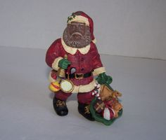 In Santa's left hand he has a toy sack and we can see candy canes, a ball, teddy bear and presents. In Santa's right hand, he is holding a bell. Santa comes with his original box. | eBay!