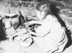 1940.45 Niña en cuclillas en la cocina de su vivienda.