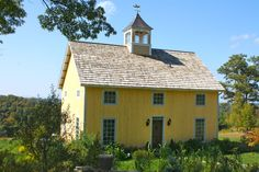 yellow barn home with cupola