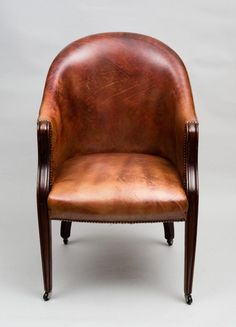 An Edwardian mahogany framed tub chair upholstered in a reddish-brown colored leather with brass nail heads, a wrap around back and square molded tapering legs on casters.