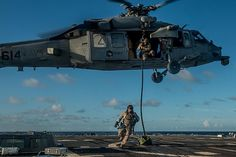 """Members of Explosive Ordnance Disposal Mobile Unit (EODMU) 5, Platoon 503, embarked aboard the USS Ronald Reagan (CVN 76), scale a rope from a helicopter assigned to the """"Golden Falcons"""" of Helicopter Combat Squadron (HSC) 12, during a fast-rope exercise on the flight deck of the Arleigh Burke-class guided-missile destroyer USS McCampbell (DDG 85)."""