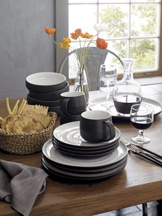 Modern and restrained in form, expressive and rustic in glaze. The artisan's hand is authentically reproduced in this stoneware pattern designed exclusively for Crate and Barrel by ceramic artist and designer Kathy Erteman at her 18th Street studio in New York City. A contemporary matte black exterior contrasts the rustic beauty of a shiny, speckled white glazed interior ringed with the subtly raised spiral associated with hand-thrown pieces. A raised clay rim features a sandy glaze that…