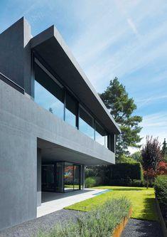 Dieses Einfamilienhaus wirkt wie ein plastisches Objekt, das sich mit dem Außenraum verzahnt. Gartenzimmer und ein bepflanztes Atrium bieten viel Grün.