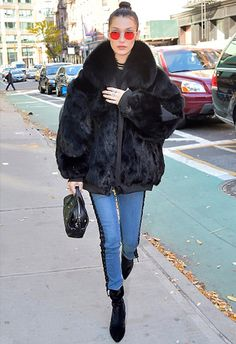 Bella Hadid wearing lace-up jeans with a black furry jacket   ASOS Fashion & Beauty Feed