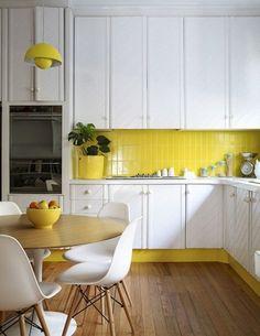 Cheerful pops of yellow brighten an all-white kitchen.