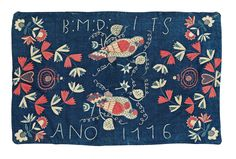 """CARRIAGE CUSHION, EMBROIDERED. """"Papegojor"""". Scania, Sweden, 1776. 60,5 x 93 cm. A blue woolen ground with polychrome embroideries of parrots, wreaths and corner bouquets as well as B:M:D: ITS ANO 1776."""