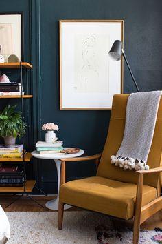 dark blue-isn green walls and mustard chair