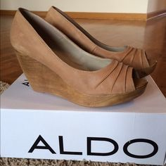 Aldo Wedge Gorgeous neutral tan/beige Aldo wedge. Beautiful ruching at toe. Genuine leather. Wood wedge. Superior comfort and style! Beautiful variations in color on leather and wooden wedge! Brand new in box! FYI, Aldo shoes run a bit on the small side! ALDO Shoes Wedges