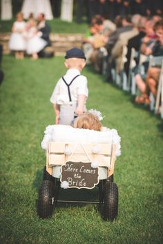love the finishing detail on this....decorated wagon for the flower girl and pulled by the ring bearer, but the wedding sign makes it....