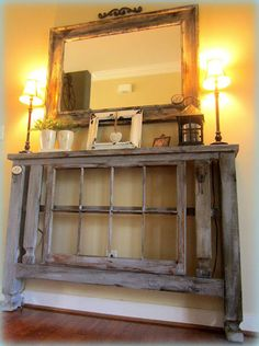 Entryway tables made from deck post with a reclaimed window frame centerpieces, painted and distressed for an aged patina, greet guest with rustic charm.