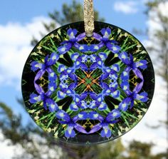 Blue iris Geometric Kaleidoscope Mandala Glass Sun Catcher titled Cerulean Credence. <br /> <br />This stunning beveled glass sun catcher illuminates my geometric mandala kaleidoscope design when light shines through it! It is 3 - ½ inches in diameter and has a beveled edge. The Suncatcher comes with a ribbon and suction cup for hanging. <br /> <br /...