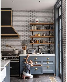 Carrara marble kitchen countertops with blue cabinets, whote subway tile with dark grout, dark stone floor, and black and brass accents - Kitchen Trends 2015