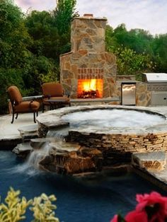 outdoor fireplace & jacuzzi with a little water fall into the pool!