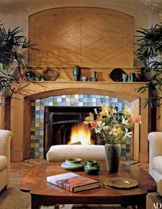Turn-of-the-century glass tiles by Tiffany & Co. surround the fireplace; on the mantel are Rookwood, Fulper and Grueby pottery. Sofa fabric by Donghia.