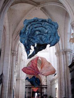 """Installation de Peter Gentenaat """"Il crée son propre papier pour réaliser ses sculptures, car il n'arrive pas à obtenir le résultat qu'il souhaite avec les papiers que l'on trouve dans le commerce. Il fait sécher la pâte humide de papier sur le cadre en bambou et cette dernière se rétrécit et se courbe comme une feuille d'arbre quand elle s'assèche. Il en résulte ces sculptures massives mais délicates qui flottent dans l'air."""""""