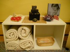 Our Peace table....Top shelf: aromatherapy pillow, running water battery operated fountain, share stone, When I Make Silence book, lotus flower candle holder and a sea shell. Bottom shelf: rugs and affirmations in a basket.