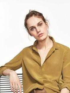 Camisa lisa, confecionada em tecido 100% de seda de amoreira. Corte reto, colarinho clássico, fecho mediante abotoadura oculta por carcela, manga comprida terminada em punho abotoado e parte inferior arredondada.
