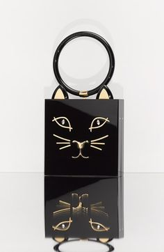 Charlotte Olympia 'Kitty' Clutch $995....A gilt cat face with sparkling Swarovski-crystal eyes lends playful charm to a polished box clutch with a dramatic, circular handle.•Clasp closure.•Fits iPhone 5, 5S and most other smartphones.•Perspex® with Swarovski crystal detailing.•By Charlotte Olympia; imported. Item #974643