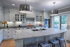 White kitchen with marble island top.  (Cabinets by Modern Design Cabinetry.)