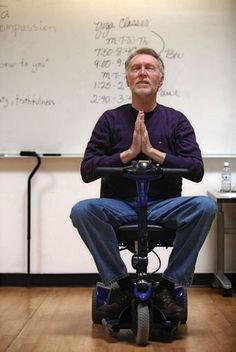 From a seat on an electric scooter, Paul MacNaughton leads a yoga class Thursday in the Fitness Center at Everett Community College.