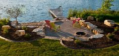 This is the idea I've had of digging straight into my hilly backyard from the sea wall and creating a large, flat area with fire pit, Adk chairs .... (M.T. Carpenter Landscape)