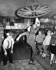 """That old wagon wheel hanging from the ceiling stirs kind of a challenge,"" said Crump Redding. Then the 61-year-old Aurora, Nebraska, man kicked his right leg up and touched the rim of the wheel — 7 feet, 6 inches above the floor. This Feb. 13, 1983 photo shows the popular frontier sport of high kicking. Redding got his kick in at Ole's Big Game Lounge in Paxton, Nebraska, where the crowd roared with approval after the feat. THE WORLD-HERALD"