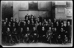 A group photo showing members of the first Dáil. In the front row are Michael Collins (second from left), Arthur Griffith (fourth from left, holding hat and stick) and Éamon de Valera (middle, beside Griffith).