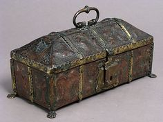 Coffret  Date: late 14th century Culture: French (?) Medium: Leather (Cuir bouilli), polychromy, silver gilt and enamel coat of arms, gilt copper alloy mounts on wood core Dimensions: Overall (handle up): 6 x 10 13/16 x 5 1/4 in. (15.3 x 27.4 x 13.4 cm) Overall (handle down): 4 15/16 x 10 13/16 x 5 1/4 in. (12.5 x 27.4 x 13.4 cm) Classification: Leatherwork Credit Line: Gift of Dr. Bashford Dean, 1923 Accession Number: 23.229.1