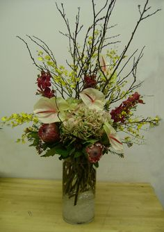 This is an arrangement featuring white anthurium, protea, red mokara orchids and branches.  See our entire selection at www.starflor.com.  To purchase any of our floral selections, as gifts or décor, please call us at 800.520.8999 or visit our e-commerce portal at www.Starbrightnyc.com. This composition of flowers is generally available for same day delivery in New York City (NYC). TR050 #flowers #floraldesign #floralarrangement #events #decor