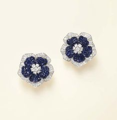A PAIR OF INVISIBLY-SET SAPPHIRE AND DIAMOND EAR CLIPS, BY VAN CLEEF & ARPELS  Each designed as an invisibly-set calibré-cut sapphire flowerhead, centering upon a circular-cut diamond cluster pistil, to the circular-cut diamond trim, mounted in platinum and 18k gold, with French assay marks and maker's marks  Signed Van Cleef & Arpels, Made in France, no. NY59586; with maker's marks for Van Cleef & Arpels