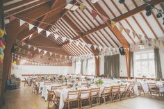 Country Village Hall with High ceiling and exposed beams - Image by  Millie Benbow Photography - A Phase Eight wedding dress for a vintage inspired village hall wedding with handpicked wild flowers and floral bridesmaid dresses.