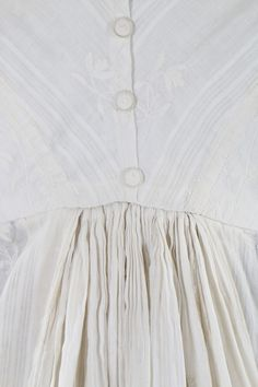A whitework embroidered empire-line muslin dress, circa 1805. with woven self-stripes and vertically embroidered foliate bands, nice back detailing with four Dorset buttons, slightly trained hem, bodice with internal linen narrow front closure flaps and remains of triangular front bodice panels. - See more at: http://kerrytaylorauctions.com/one-item/?id=119&sub&auctionid=402#sthash.GXni9oLC.dpuf