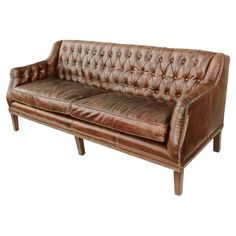 Highlighted by button-tufted leather upholstery, this handsome sofa brings rich style to your living room or library decor.  Product...