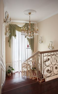 Dramatic staircase highlighted by an asymmetrical green swag with tassels and crystal lighting.