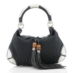This collectible Gucci bag is made from black GG canvas with tonal leather trim, oversized tassels, bamboo details, and silver-tone hardware. Features include a rolled handle, fold-over closure, and fully lined interior with one open pocket and one zippered pocket.
