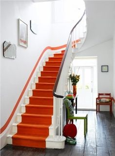 Tangerine orange carpeted stairs; it can also be painted. A fabulous pop of colour.