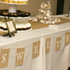 The dessert table featured a three tier display of cupcakes, baked by CupCake, and more s'more makings. Photo Credit: Bellagala