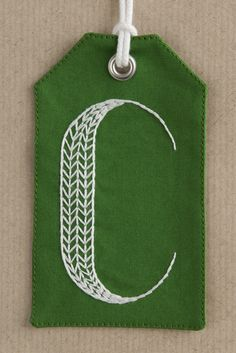 Squibblybups hand-embroidered gift tag with the initial 'C' in herringbone.