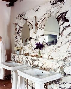 nice marble wall with double pedestal sinks in bathroom