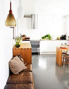 High gloss floors, comfy leather bench & warm woods in the kitchen