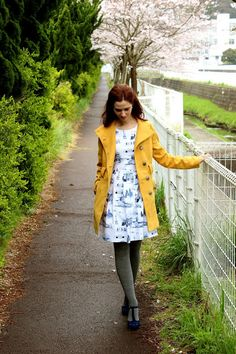 The dress print is just fab and love the pairing with the hunter green tights and yellow coat-odd mix of colors that works so well!-and the black retro heels.