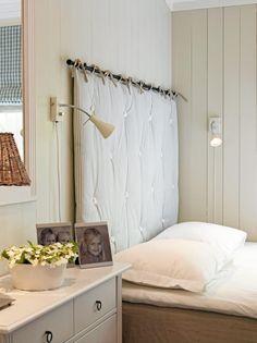 Et lekkert soverom i duse fargetoner skaper et inntrykk av ro og renhet, mens bruken av blomster og familiebilder tilfører et personlig preg. Sengegavlen er festet over sengen på en gardinstang.