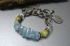 This piece is made with light blue aquamarine nuggets and a 10mm yellow-green jasper and blue quartz gemstone. Intermixed in the piece are sterling silver and rhinestone spacers. The silver mixed metal chain is adorned with charms. As is it will fit a 6 1/2 to 7 inchwrist but it can be adjusted to fit any wrist size. Just let me know your wrist size in the memo to seller section upon check out.