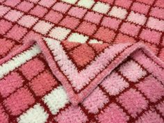 Adorable baby blanket /afghan made with soft strawberry pink colors in a cute square pattern.