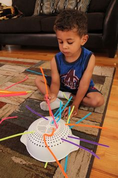 Preschool activities can be fun, simple, and cheap like this one using pipe cleaners and a colander to practice fine motor skills.
