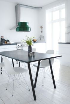Vitra's Eames Plastic Side Chairs in a nice kitchen and eating area.