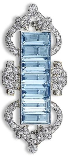 An Art Deco aquamarine and diamond brooch. Set with a row of baguette-cut aquamarines, within a stylised frame of openwork design, set throughout with old round brilliant-cut diamonds, width 50mm. #ArtDeco #brooch